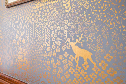 Gold flowers and deer with antlers painted on a grey wall