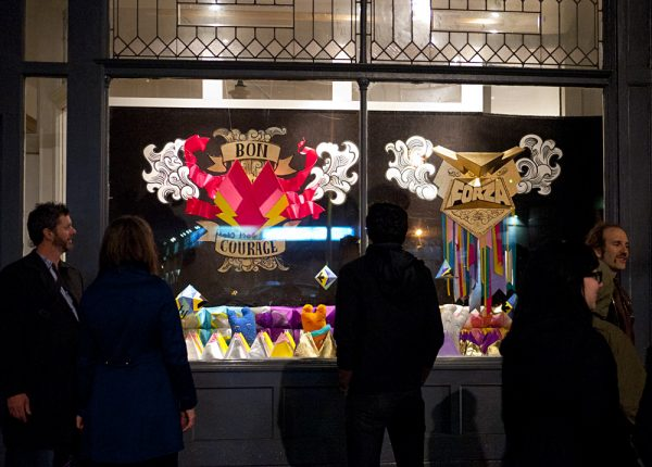 Night view of the installation with silhouetts of viewers in fron to fhe bright windows.