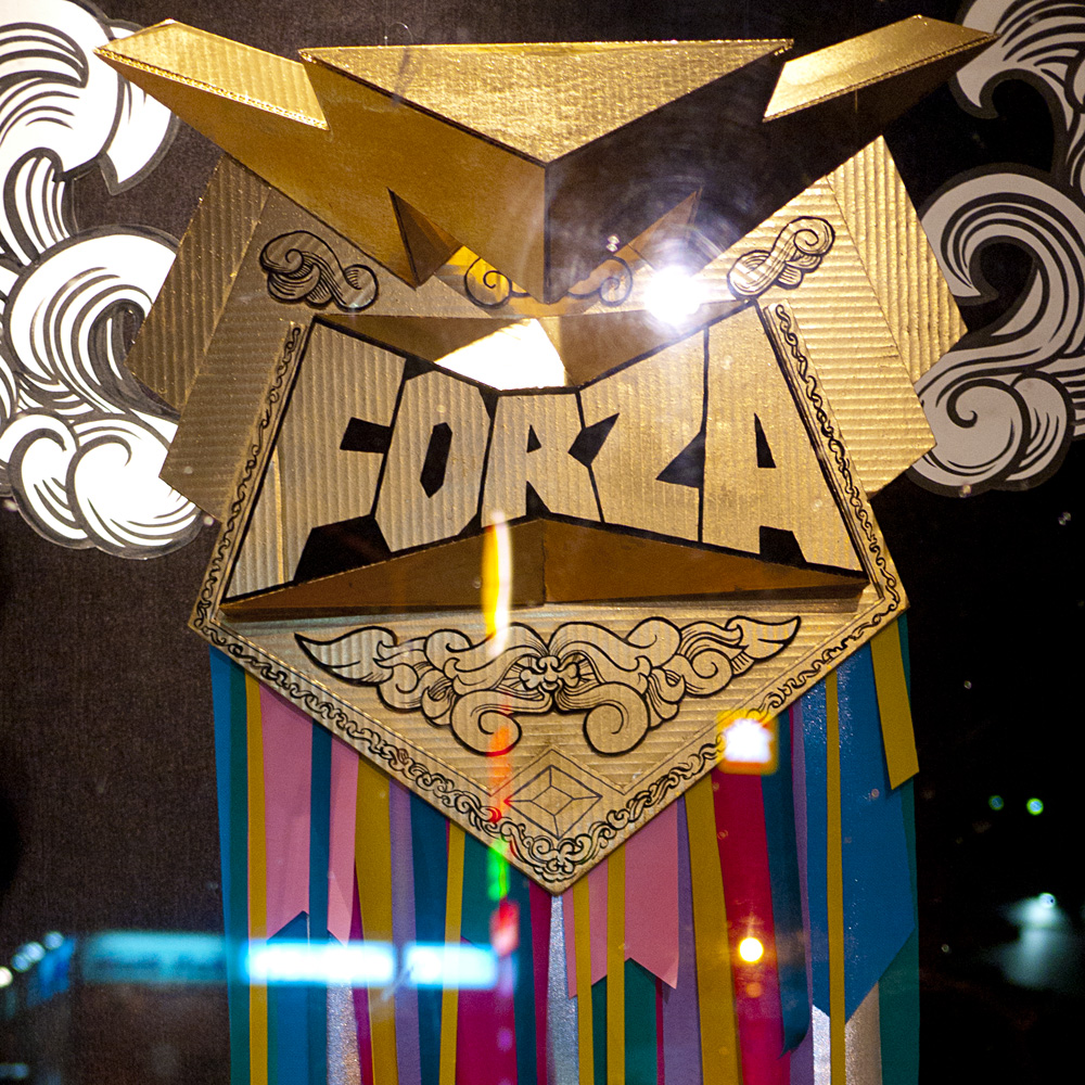 Sculpture made of cardboard and gold spray paint with the word Forza and multi-colored ribbons.