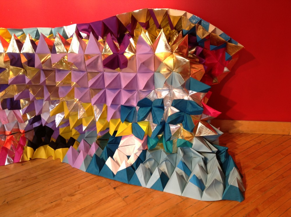 Pyramidal quilt of many colour hangs semi vertically.