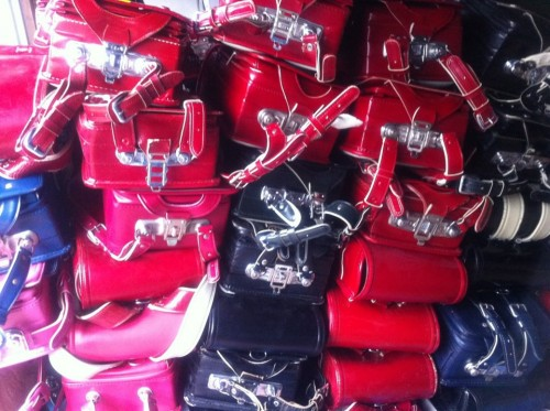 Pile of pink, red, blue, and black Japanese student backpacks
