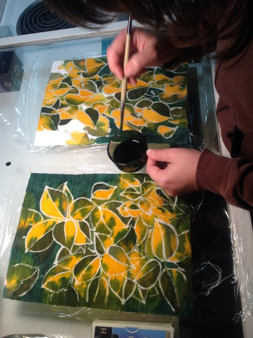Painting batik panels with dye.
