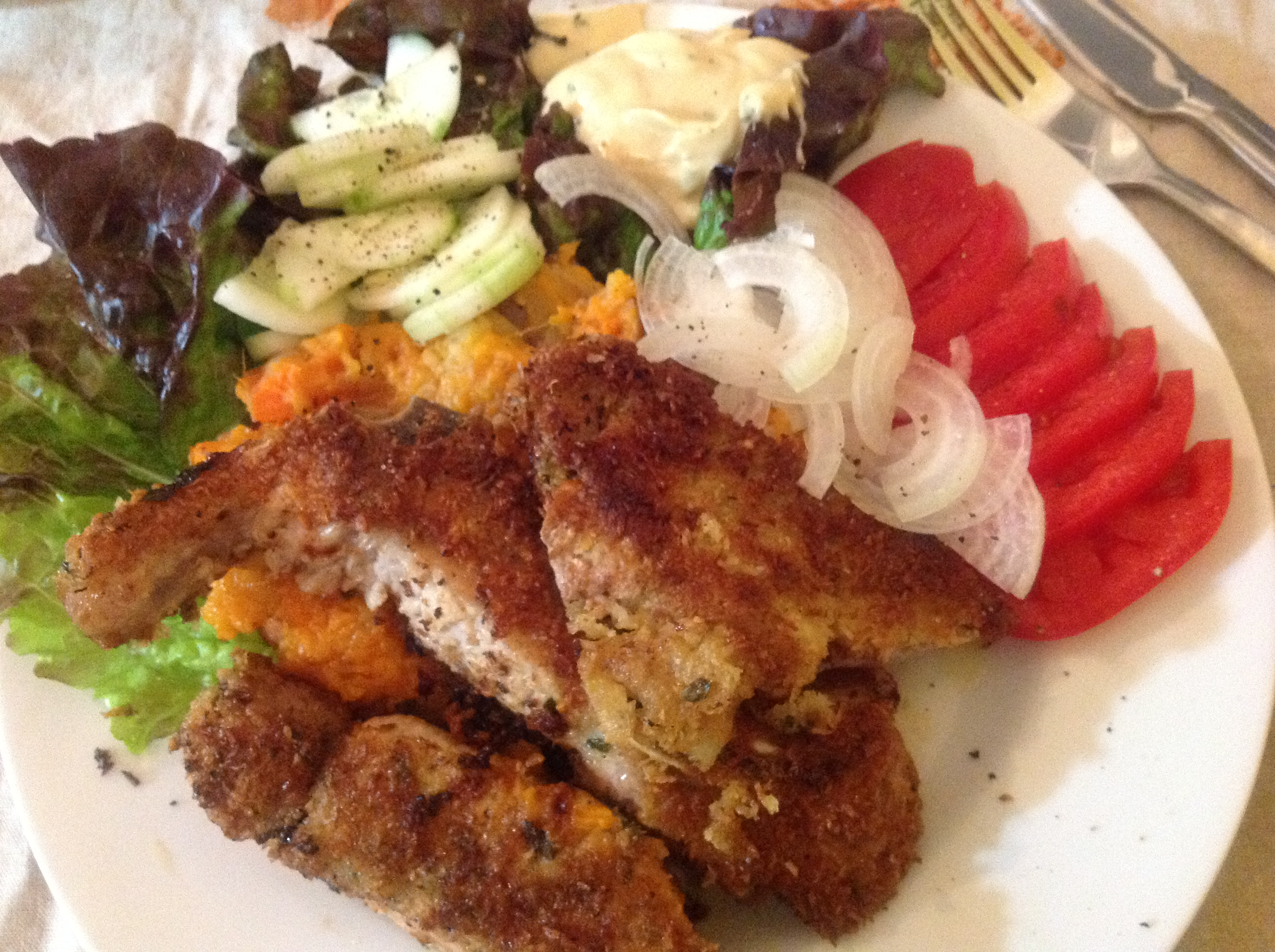 Breaded, fried meat on a white plate with vegetables