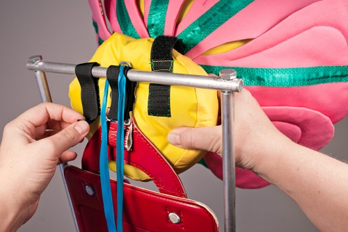 Velcro and ribbons are used to attach the flower head to the top of the backpack sculpture.