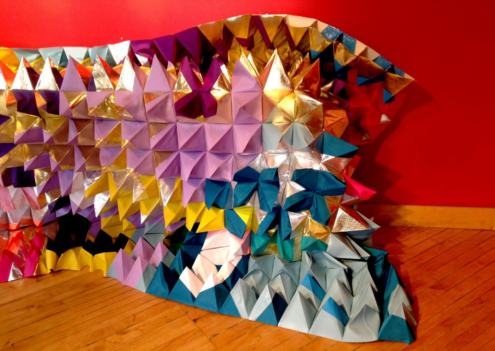 Colourful geometric 3D quilt slumped against the wall.