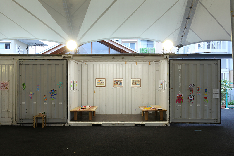 Art exhibition in a container in the communal area of the temporary housing complex.