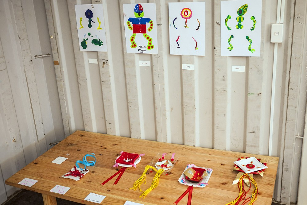 Drawings and small sculptures are hung on a metal wall and rest on a wooden table in a container housing exhibition in Onagawa, Japan.