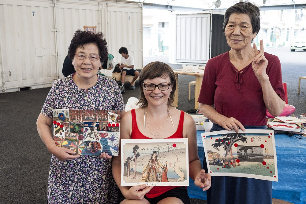 The Canadian artist Magda Wojtyra and two senior workshop attendants show off their collages.