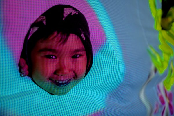 A child's face with purple and blue projected light.