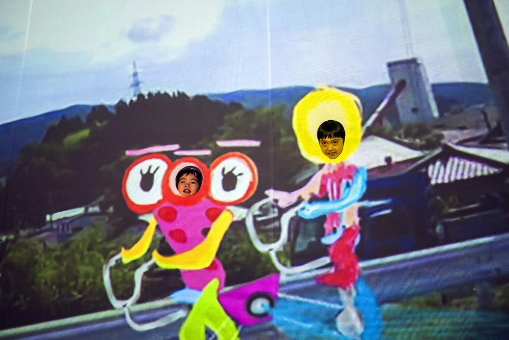 Video animation installation of two children riding a flying tandem bicycle.