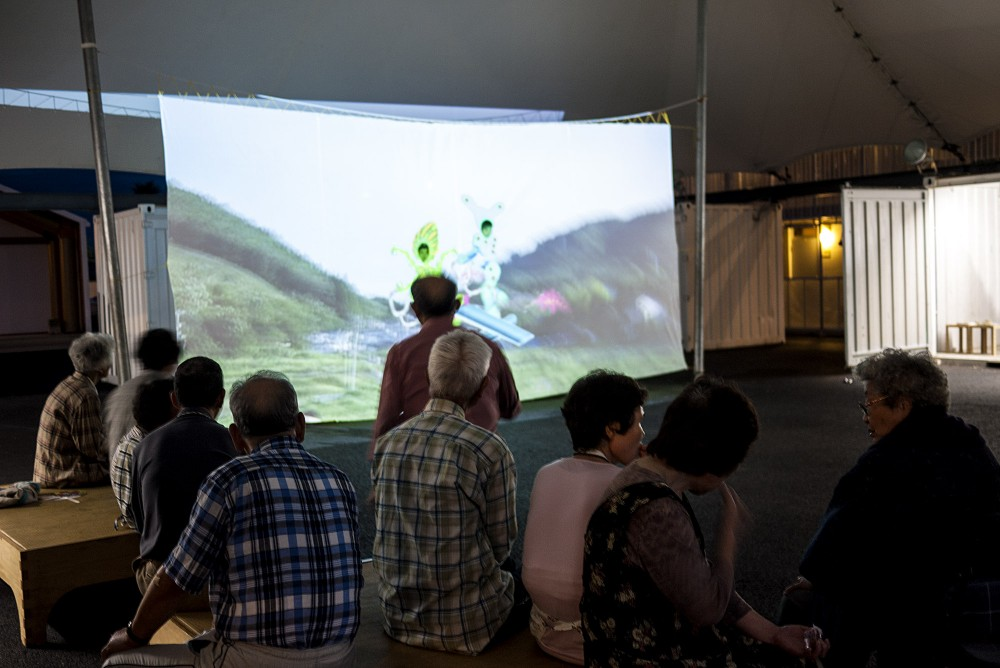 People sitting on benches look at a video projection on a big screen.