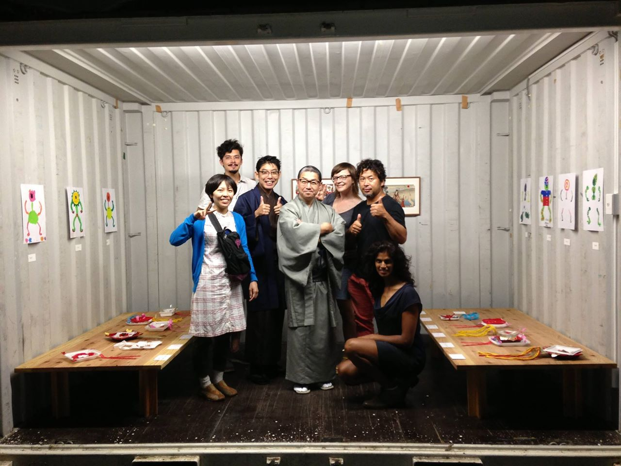 Posing inside art exhibition steel container with organizers and fellow artists