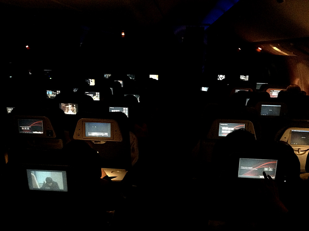 Screens on the backs of seats in a dark airplane cabin.
