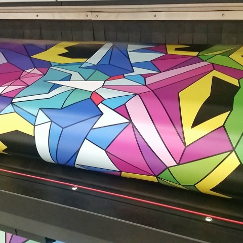 Colorful geometric print being printed and rolled by a large format banner printer.