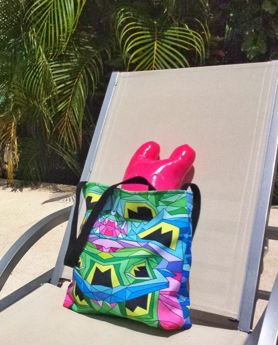 Colorful geometric tote on a deck chair by the pool.