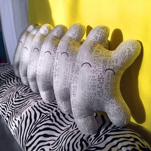 Row of plushies on a yellow background with a zebra bolster.