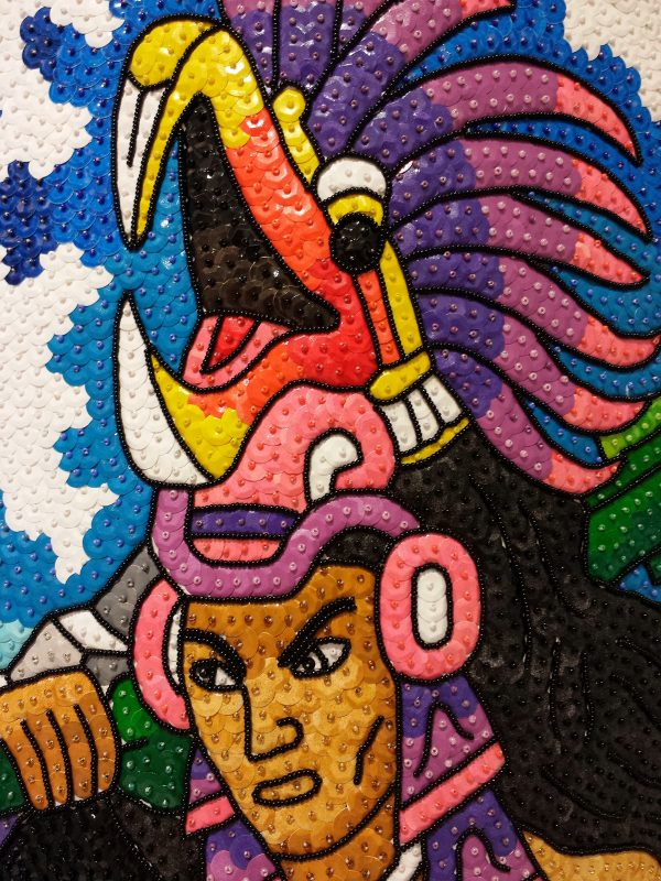 Detail of the Aztec warrior's head with the plumed serpent headdress.