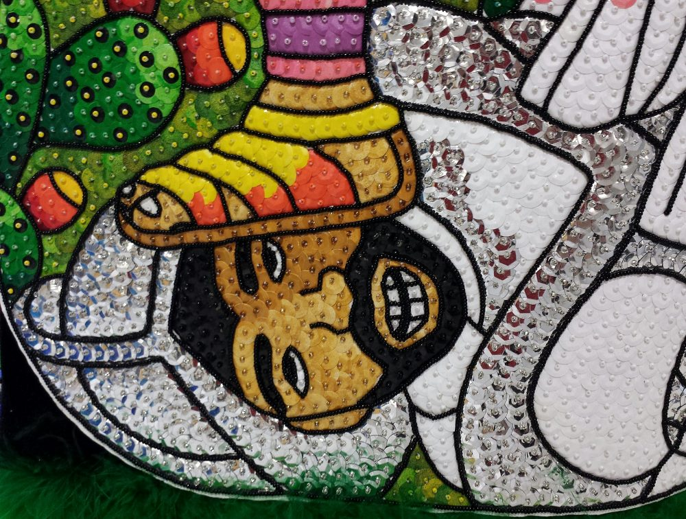 Beadwork showing the still-alive conquistador knight's head under the Aztec warrior's foot.