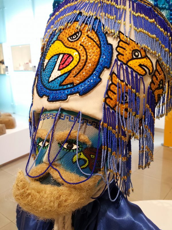 Closeup view of the child costume's head. The entire face is made of a painted mesh so that the wearer can see out. The beard is made of wool.