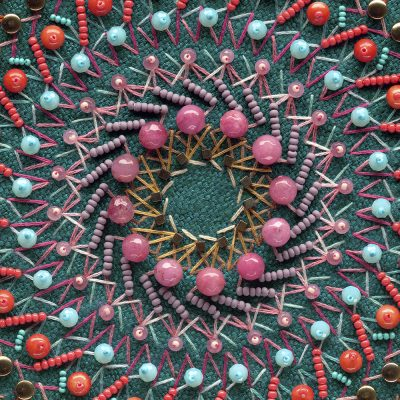 Embroidered mandala detail with blue, coral, and purple beads arranged in precisely organized rows.