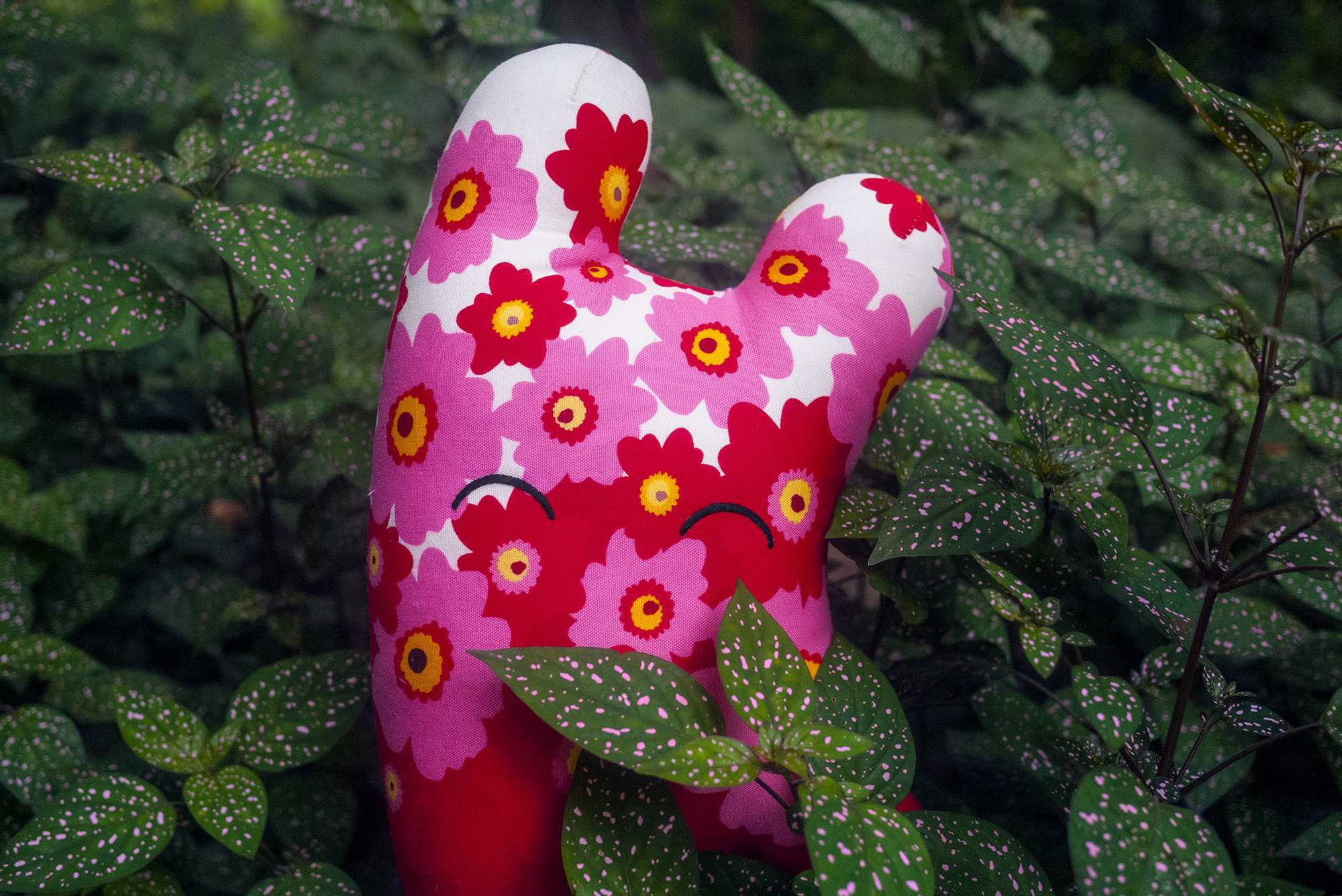 Happy Sleepy, a stuffed toy made by Magda Wojtyra, posed with matching plants with pink dots on the leaves.