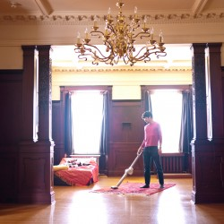 Marc vacuuming mansion