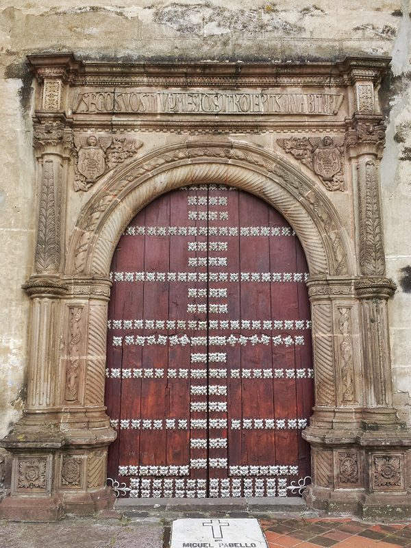 Carved stone frame and metal studded wood door